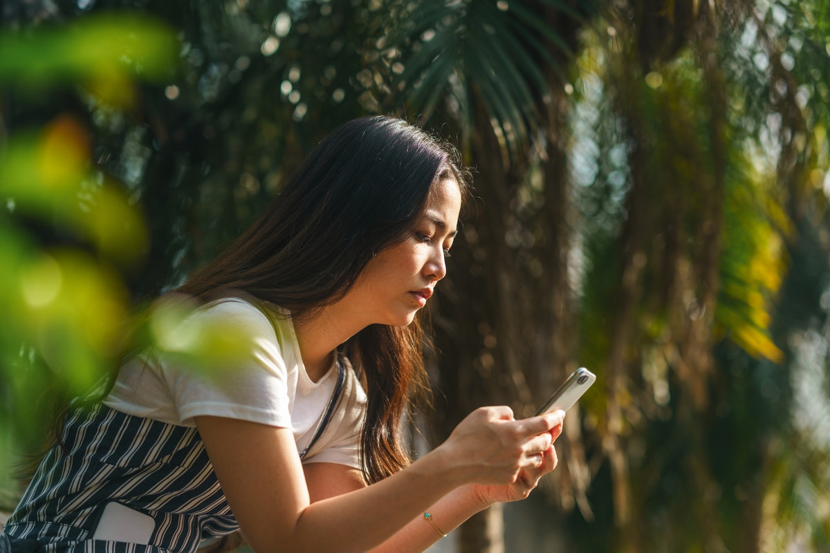 A young woman is using a smart phone among palm tree leaves.