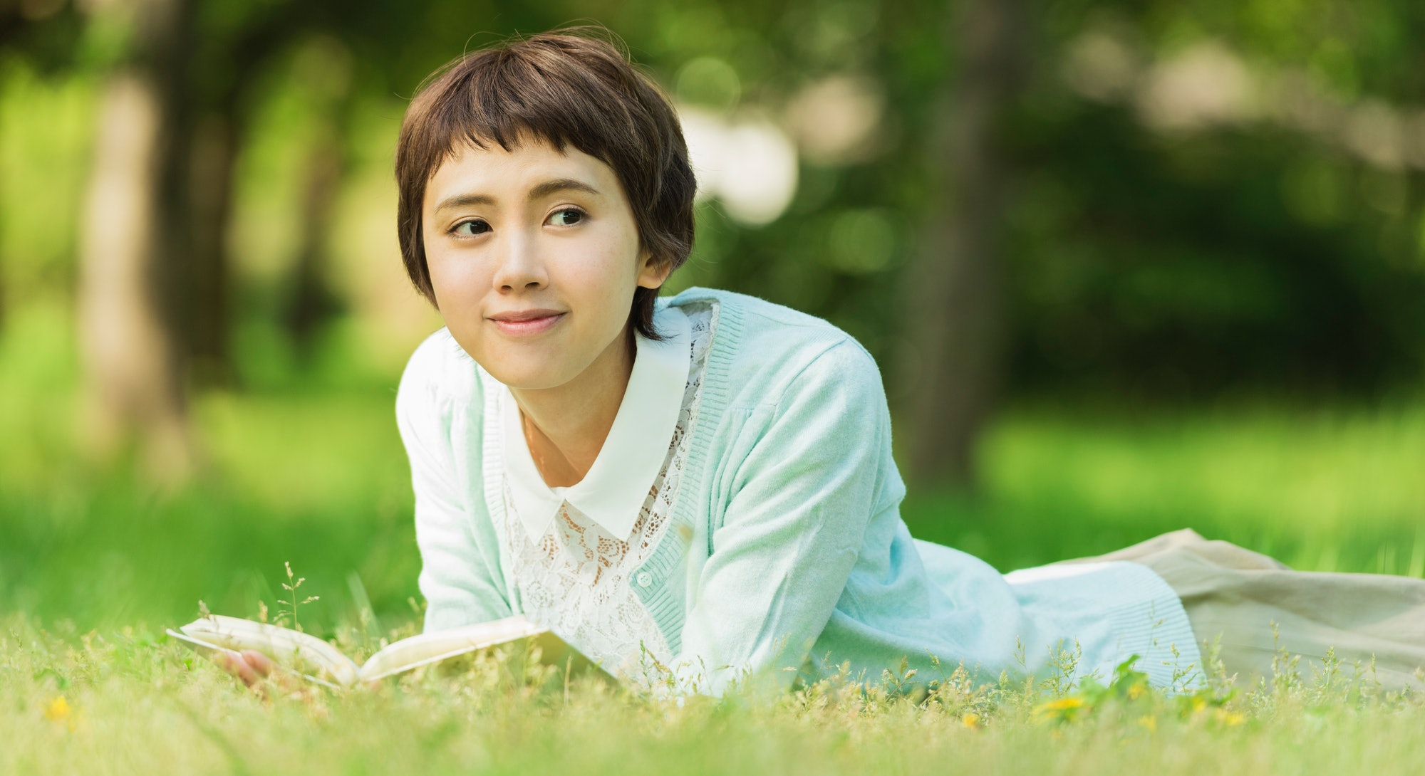A smiling, femme Asian person with short hair lies in the grass reading a book.