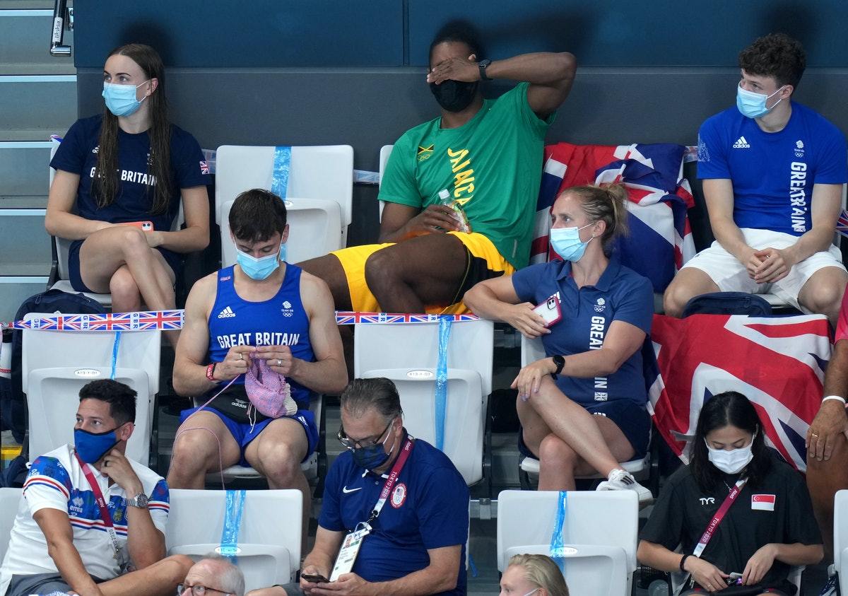 Great Britain's Tom Daley knits in the stands during the Women's 3m Springboard Final at the Tokyo A...
