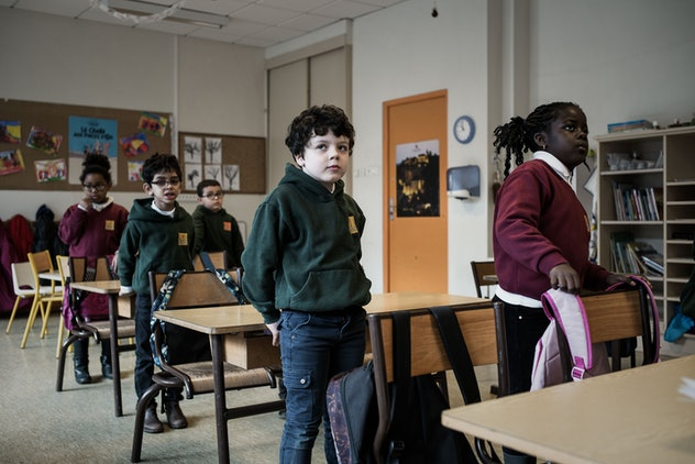 French students wear casual school uniforms of red sweaters and green hoodies with jeans