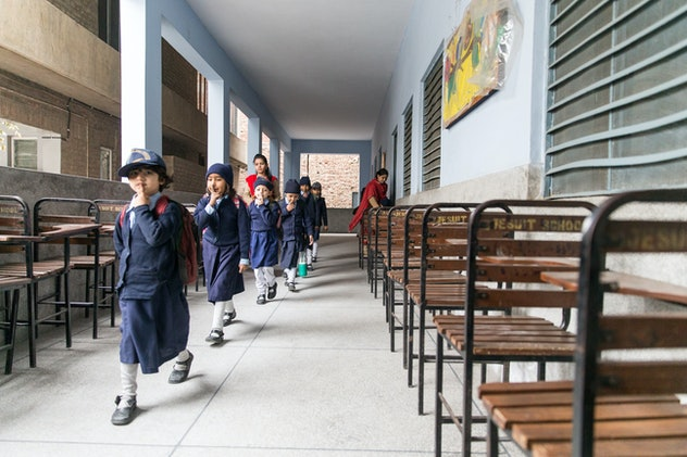 A group of school children in school uniforms of long navy skirts and matching tops at the Saint Mar...