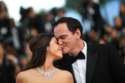 TOPSHOT - US film director Quentin Tarantino (R) kisses his wife Israeli singer Daniella Pick as the...