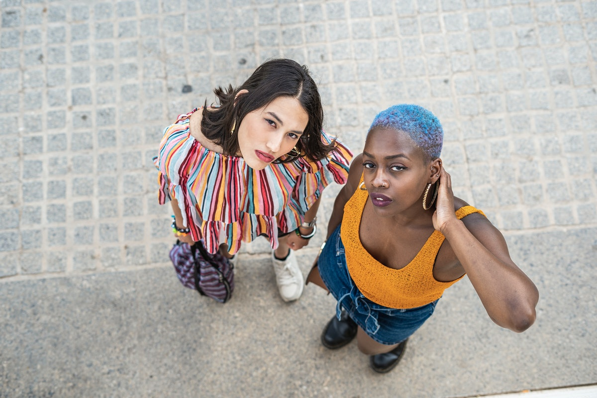 Two women — one Leo, one Virgo — looking up at the camera, wondering their friendship compatibility.