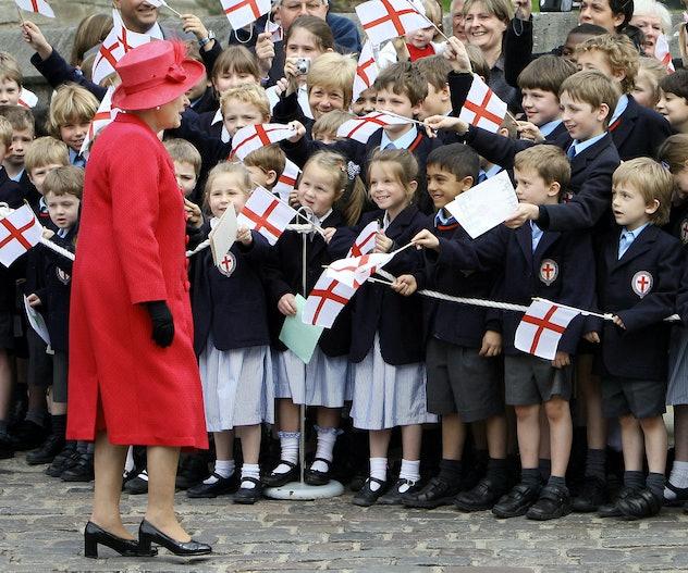 British school children dressed in uniform of blue dresses, gray shorts, and dark blazer greet Queen...