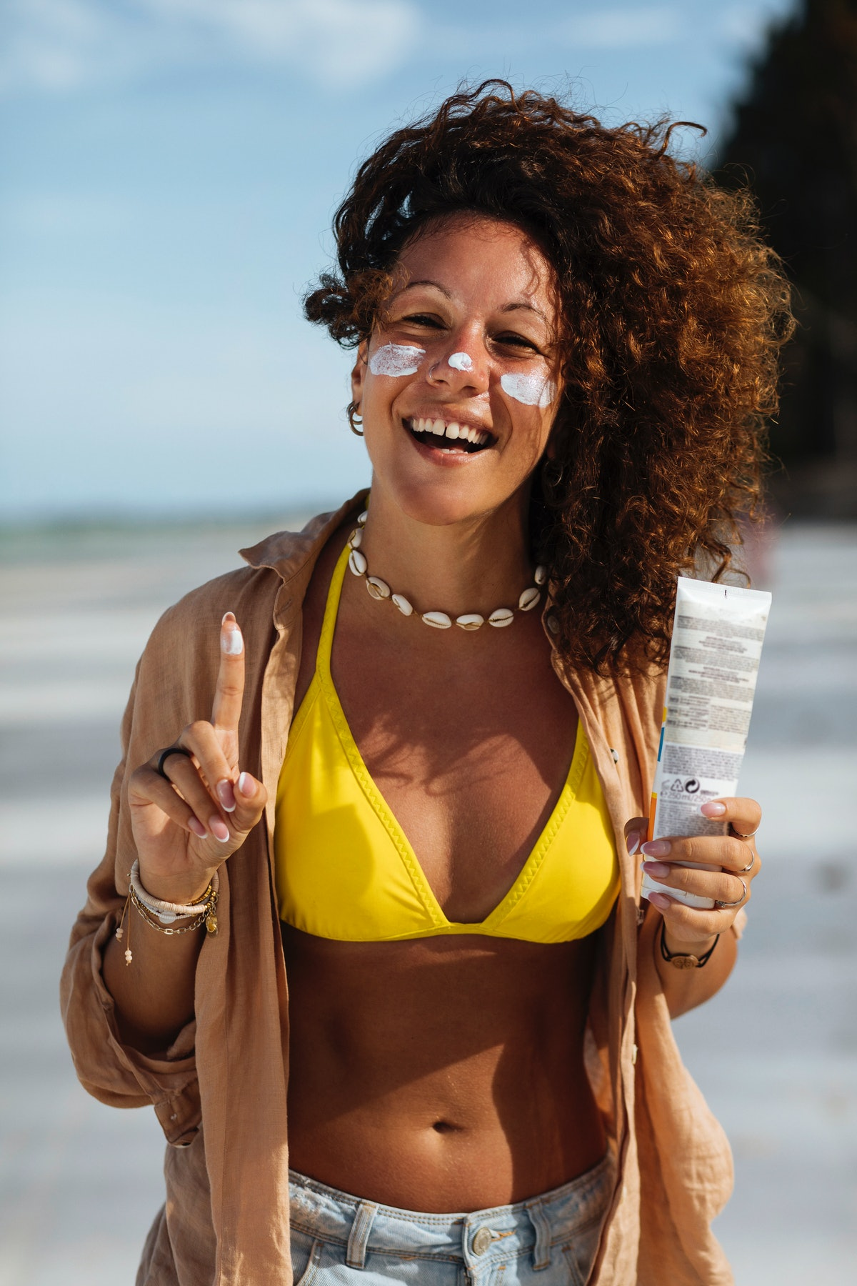 A tan young woman with curly hair laughs while applying sunscreen to her face on the beach