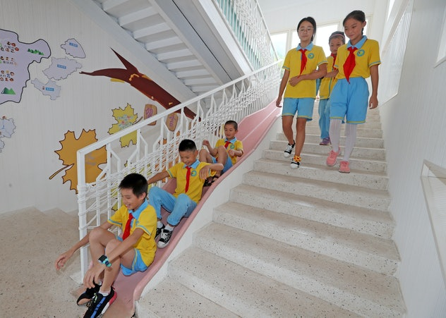 Chinese children wear bright blue and bright yellow with red ties as a school uniform. The girls tak...