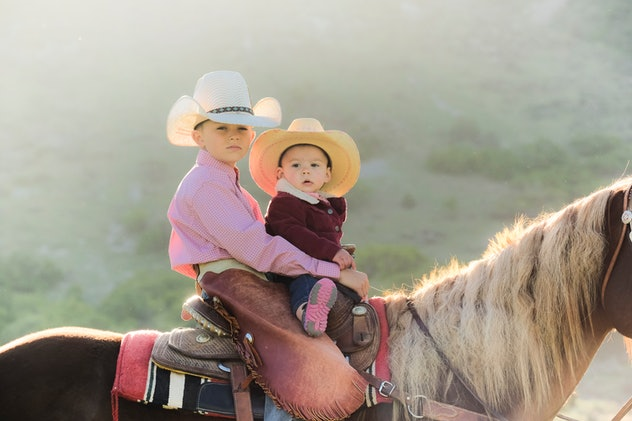 Young Boy Rides His Horse With His Baby Cousin As His Dad Watches Them