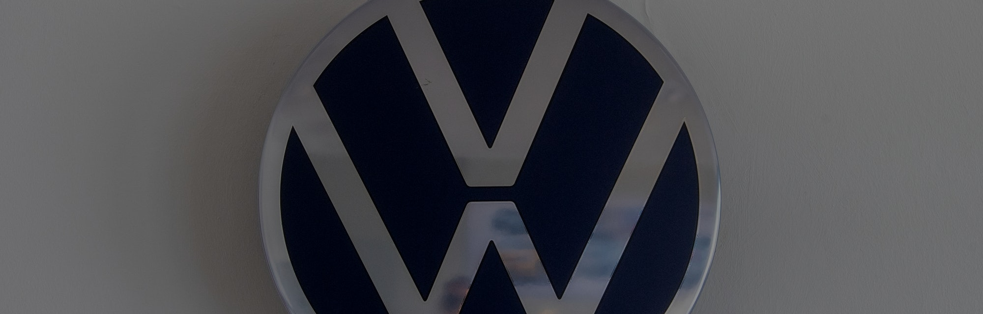 23 June 2021, Saxony, Zwickau: A plug leads from a VW logo to a socket in a conference room at the V...
