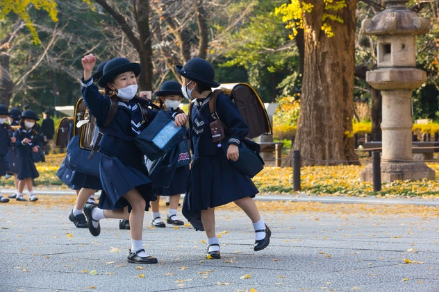 Japanese elementary school girls students dressed in traditional uniforms while wearing face masks w...