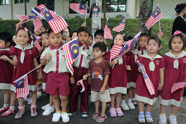 Schoolchildren wave Malaysia flags wearing red and white school uniforms