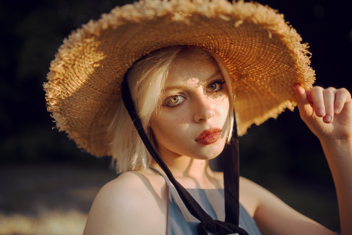 young woman wearing straw hat gazes into camera, after reading about the best day in September 2021 ...