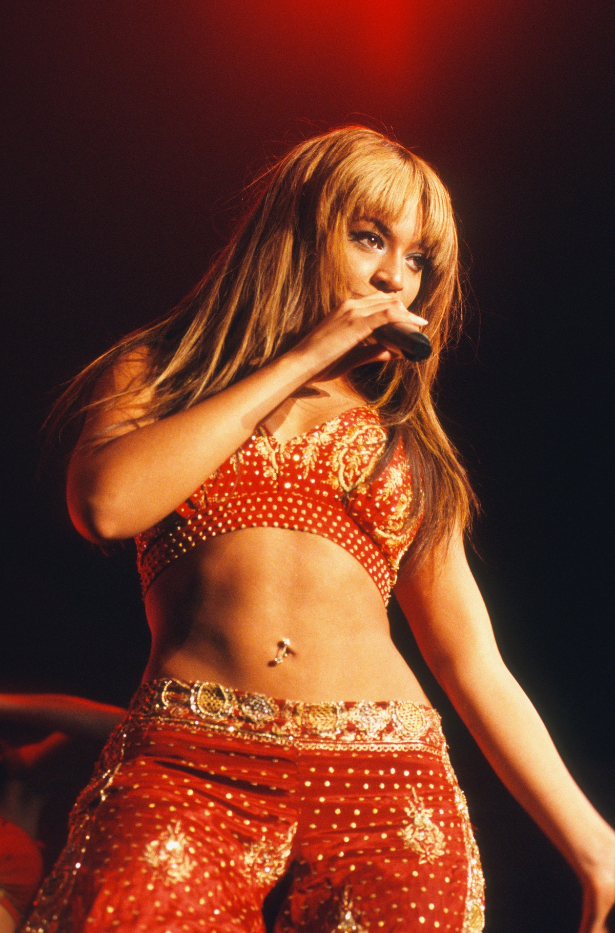 Beyonce in a red and gold outfit with her belly button on show in the Netherlands in 2003.