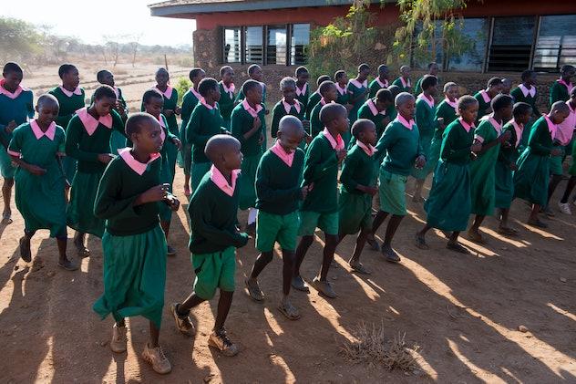 Kenyan school children dancing in school yard in green uniforms and pink collars