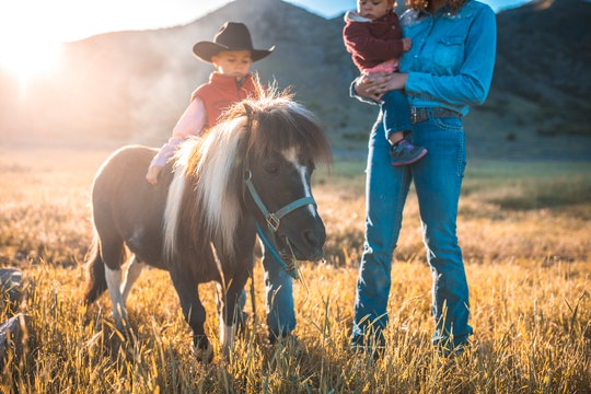 Western female rancher walking with brother and baby sister and pony through sunny Utah grassland.