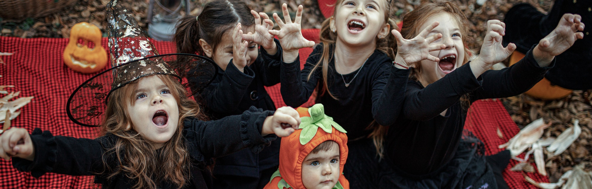 Little girls dressed playing as witch at Halloween in the forest