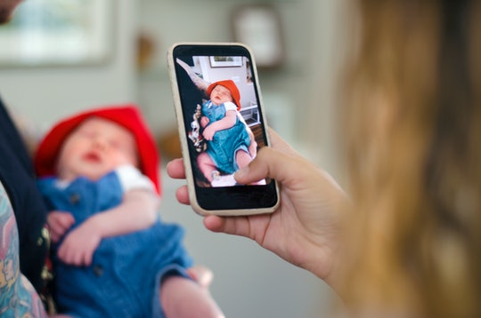 A parent snaps a photo of a newborn baby on a cellphone amid news Apple is rolling out a new feature...