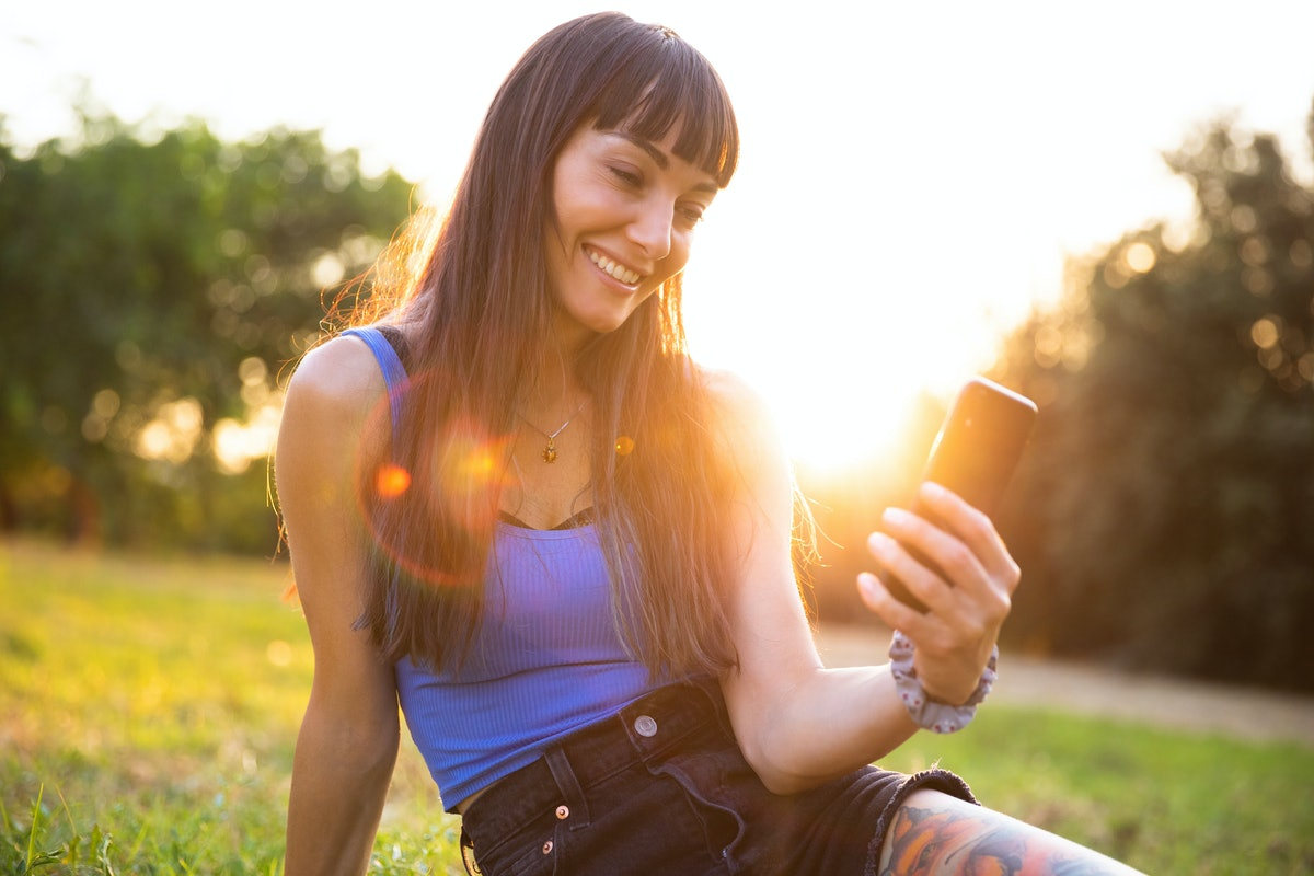 Young women using smartphone outdoor at sunset, having the best week of August 30, 2021, per her zod...