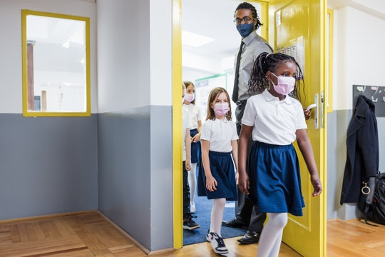 Back to school. Primary School Teacher and students entering a classroom