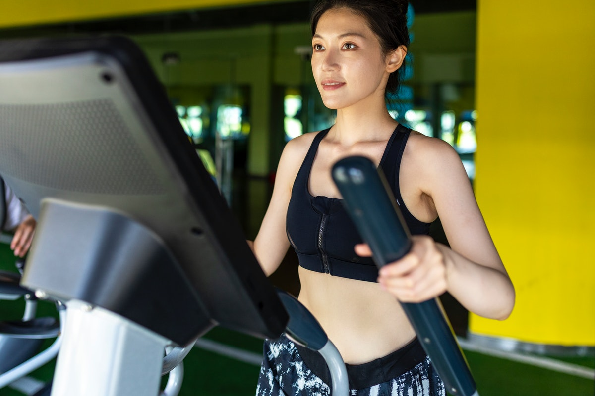 A person works out on an elliptical. Ellipticals can help ease soreness after a tough workout.
