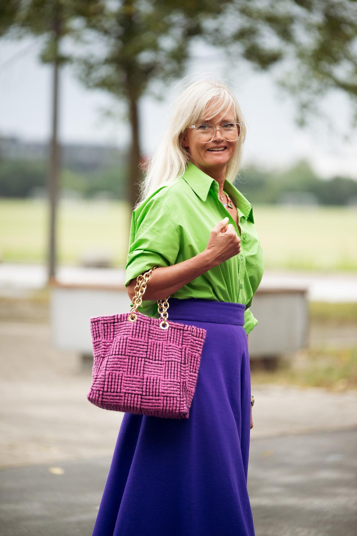 COPENHAGEN, DENMARK - AUGUST 10: Mette Sorrig wearing bright green shirt, long purple maxi skirt, pi...