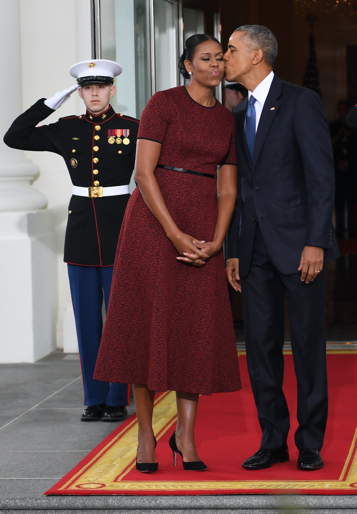 US President Barack Obama and First Lady Michelle Obama kiss as they prepare to greet President-elec...