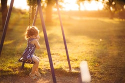 Cute little lonely sad girl swinging at sunset in public park.