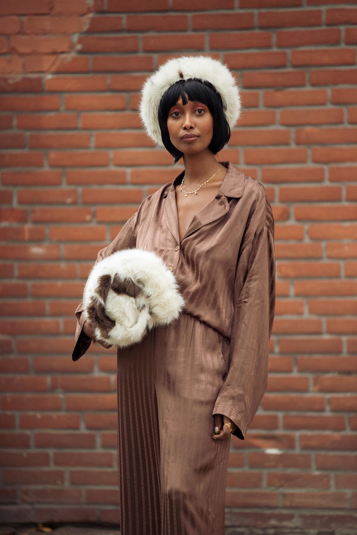 COPENHAGEN, DENMARK - AUGUST 10: Mona M. Ali wearing brown silk suit, fur har and fur bag outside Ge...