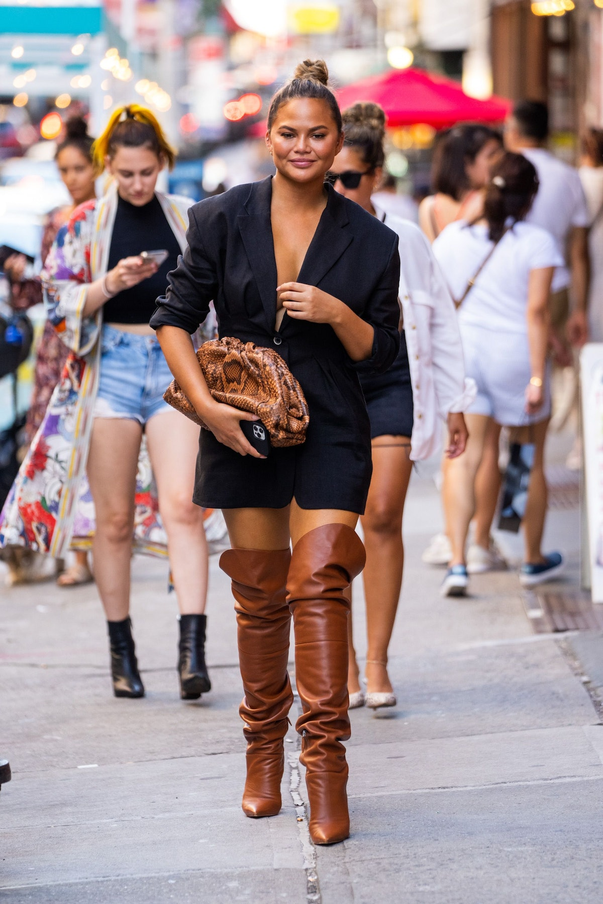 Chrissy Teigen is seen in SoHo wearing a black outfit with boots in July 2021.