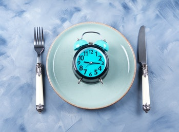 Intermittent fasting concept with blue alarm clock on empty dish with silverware
