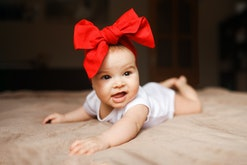 Little beautiful girl lying on the bed bow on her head smiling happy 3-4 month