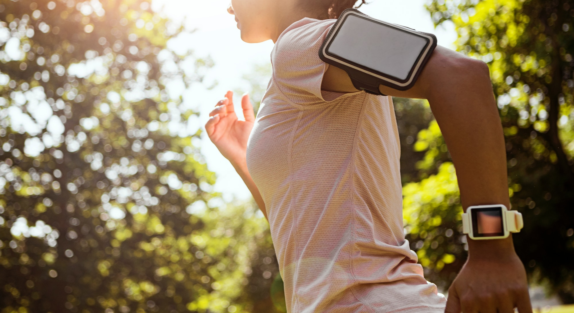 A person wears their phone on their arm as they go for a run in a park. Yes, you can work out while ...
