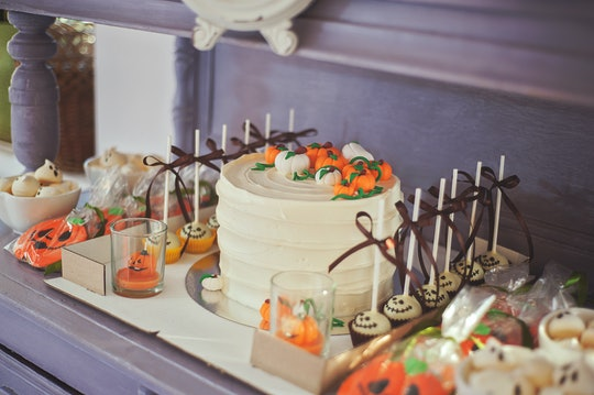 Dessert table with Halloween-themed cake, cake pops, cookies, and cupcakes