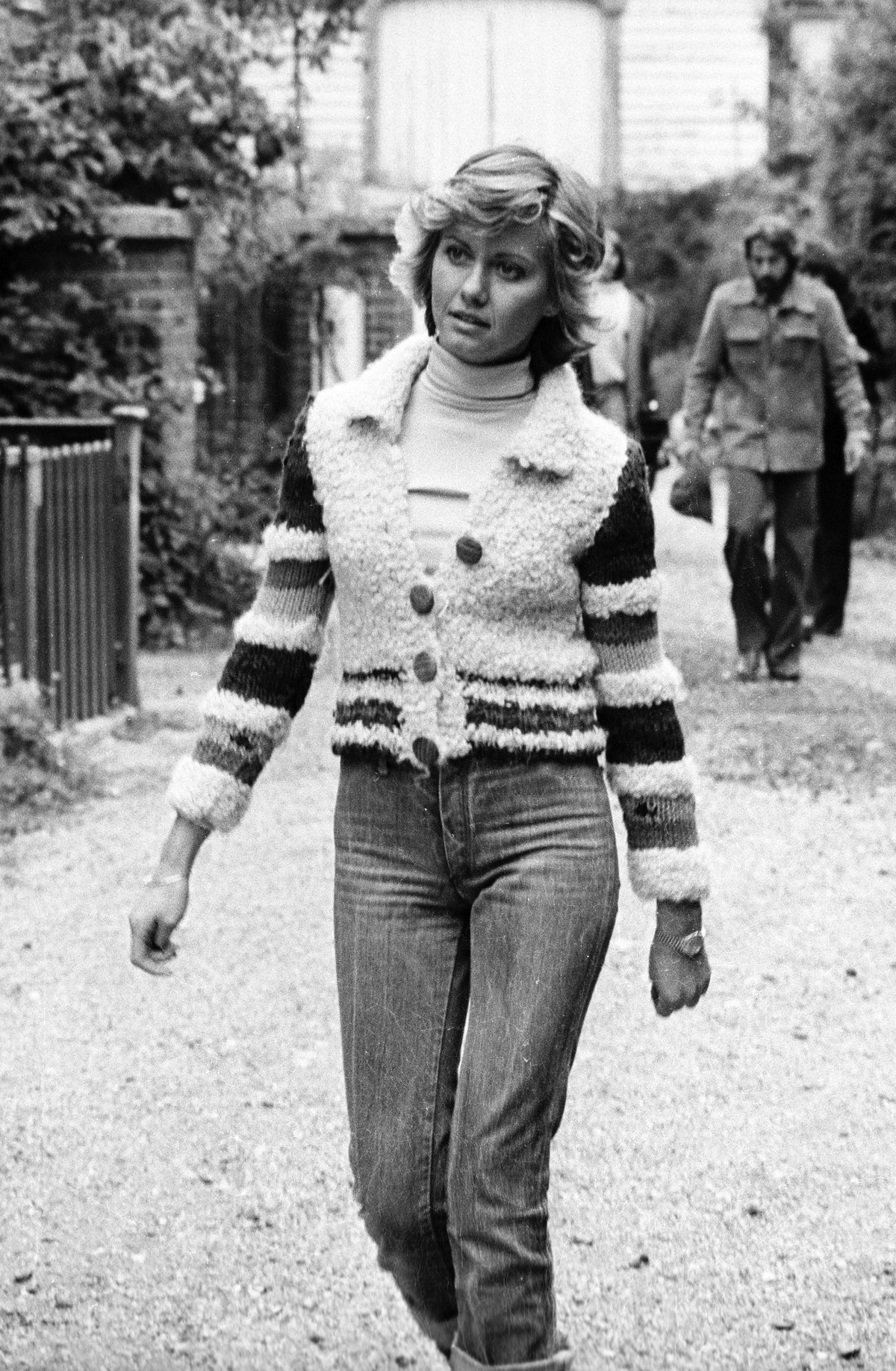 Actress and singer Olivia Newton-John wears cuffed jeans and a fuzzy cardigan while filming her firs...