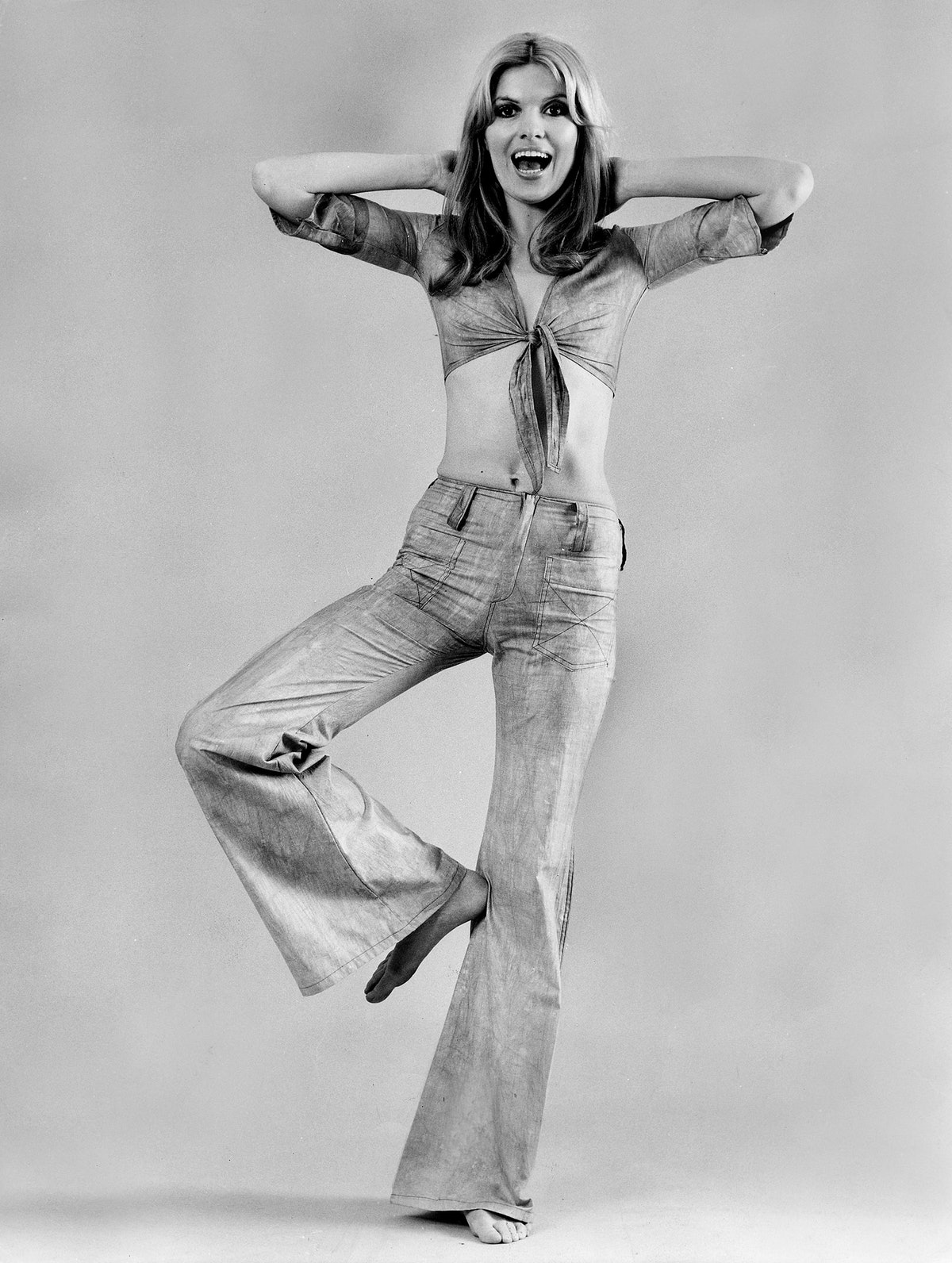 A woman wears flared jeans and a tie-front top in an advertisement in the 1970s, Germany.