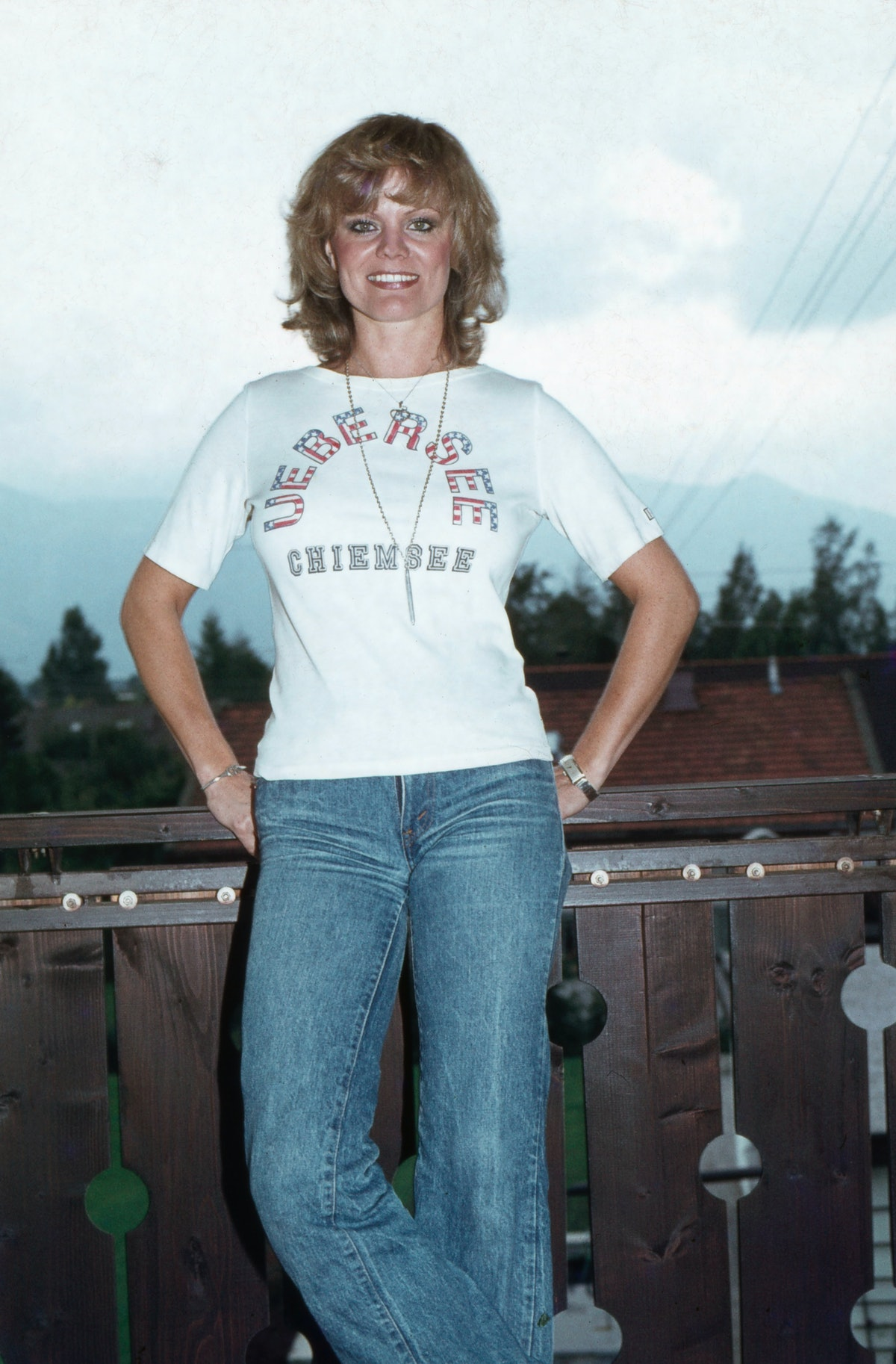 German actress Christiane Ruecker wears bootcut jeans and a graphic white tee, Germany, 1970s.