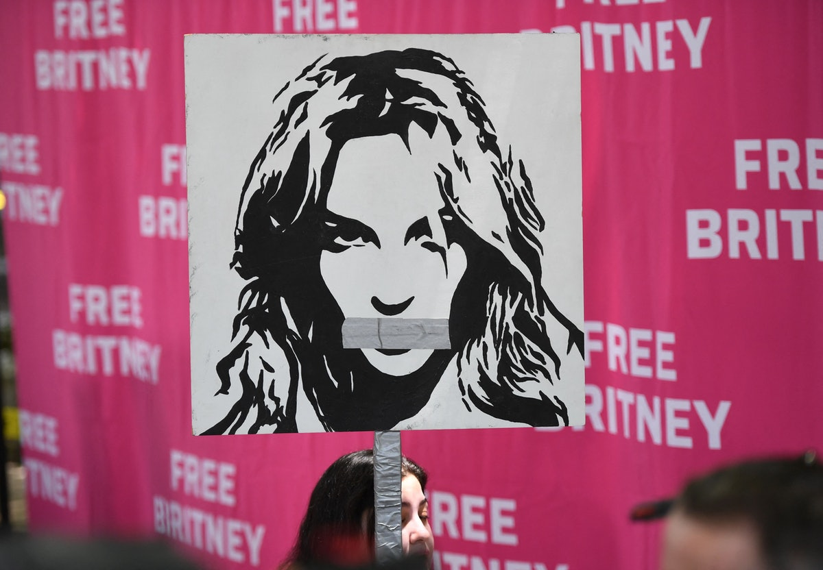 A woman holds a poster of Britney with her mouth taped shut as fans and supporters gather outside th...