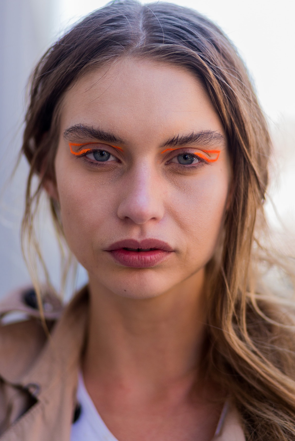 A white young model demonstrates how to wear bright orange graphic eyeliner