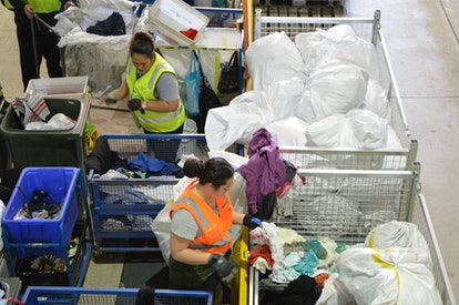 This photo taken on July 24, 2018 shows workers sorting out clothing at the St Vincent de Paul Socie...