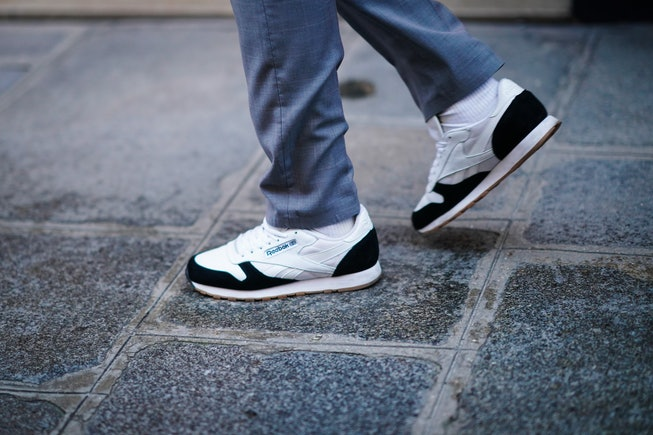 PARIS, FRANCE - DECEMBER 09: A passerby wears gray pants, Reebok black and white sneakers shoes, on ...