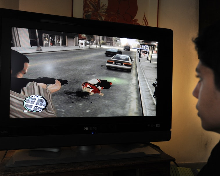 A teenager is playing with the new popular video game Grand Theft Auto IV that has been on the marke...