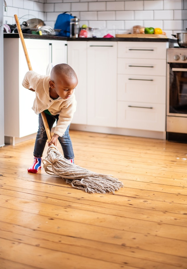 Cute little African boy trying to help around the house by cleaning the kitchen floors with a mop