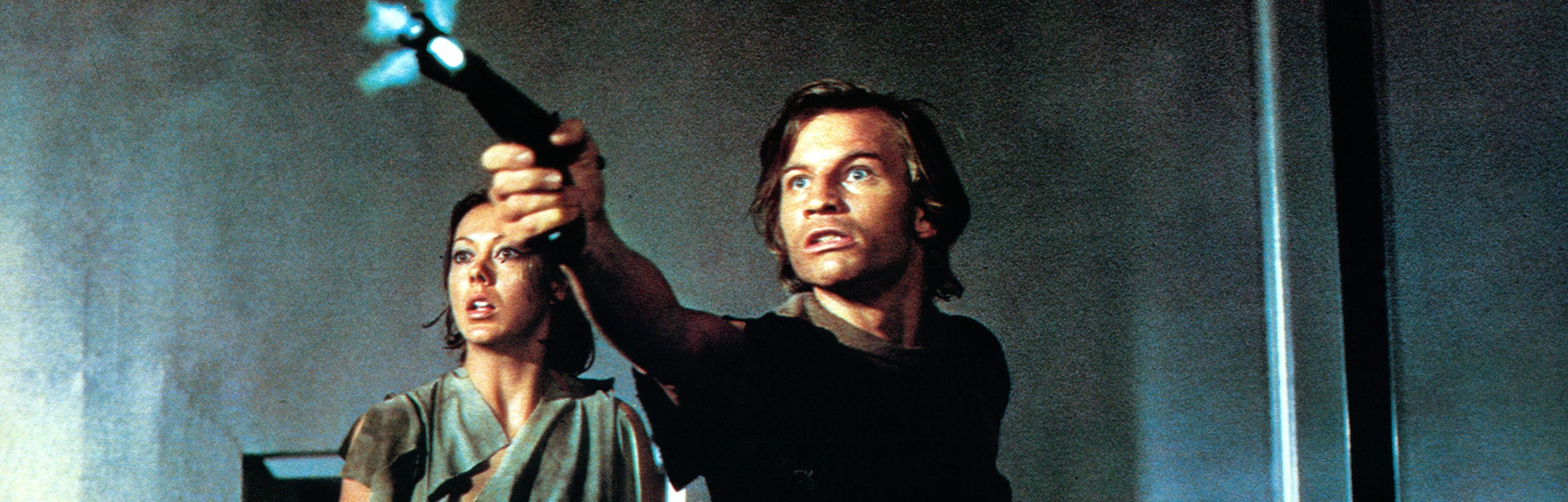 Jenny Agutter watches as Michael York shoots a gun in a scene from the film 'Logan's Run', 1976. (Ph...