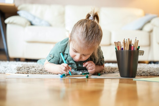 Little girl laying on living room floor, coloring and drawing.