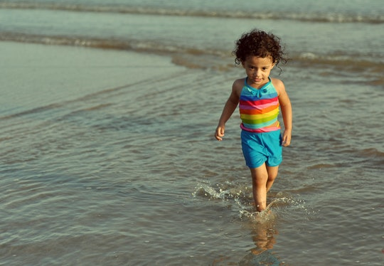Toddler walks on beach.