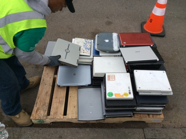 A man places a laptop computer on a skid at the Safe Disposal program, organized by the government o...