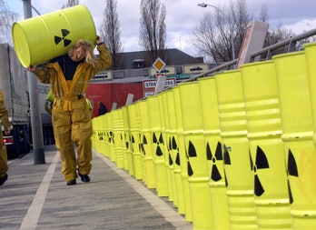 A Greenpeace militant carries a drum painted with a radioactivity sign 13 March 2001 on the Pont de ...