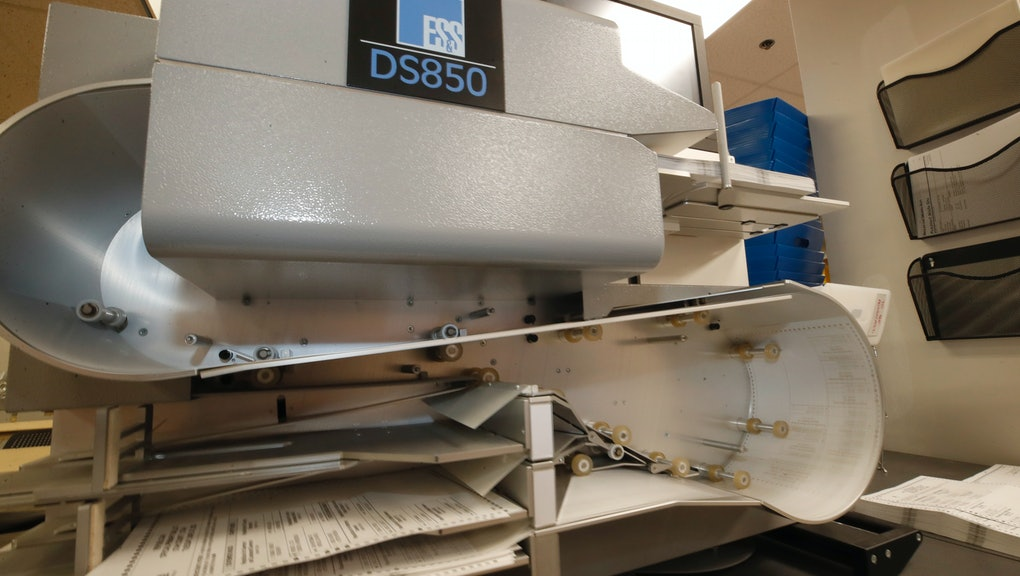 PROVO, UT - JUNE 30: A high speed counting machine processes cast ballots at the Utah County electio...