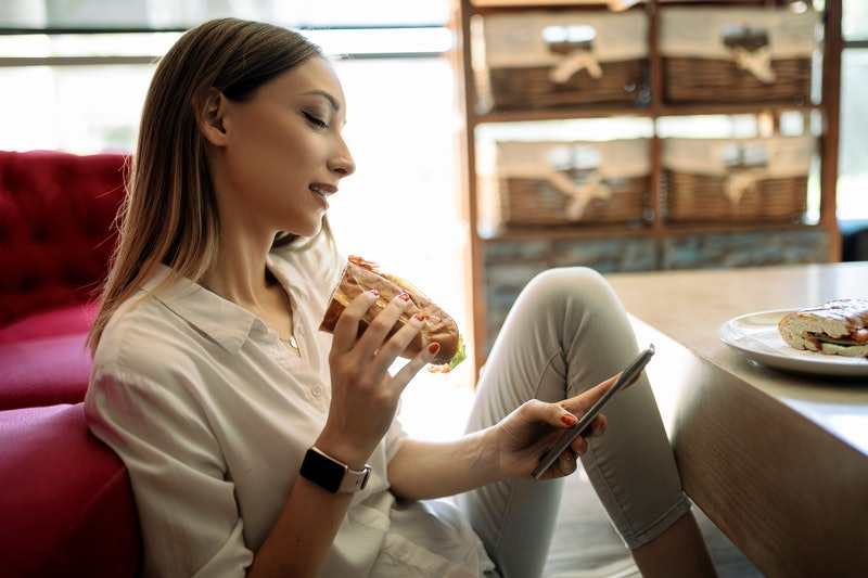 A person sits on the floor in front of their couch, texting and eating a sandwich. Reaching out to r...