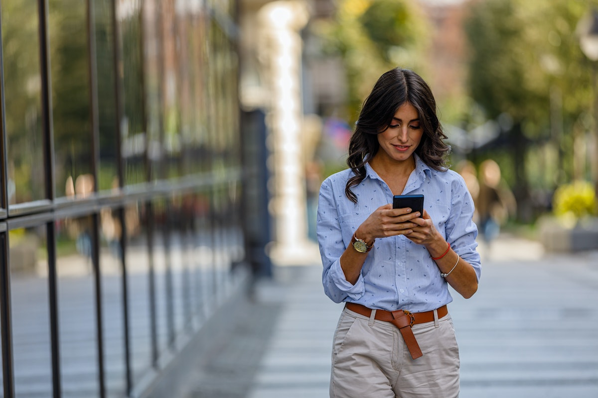 Successful and Confident Younger Woman is Walking Through the City and Typing Messages on her Smart ...