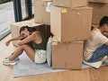 two roommates who might have a toxic relationship surrounded by boxes in their apartment.